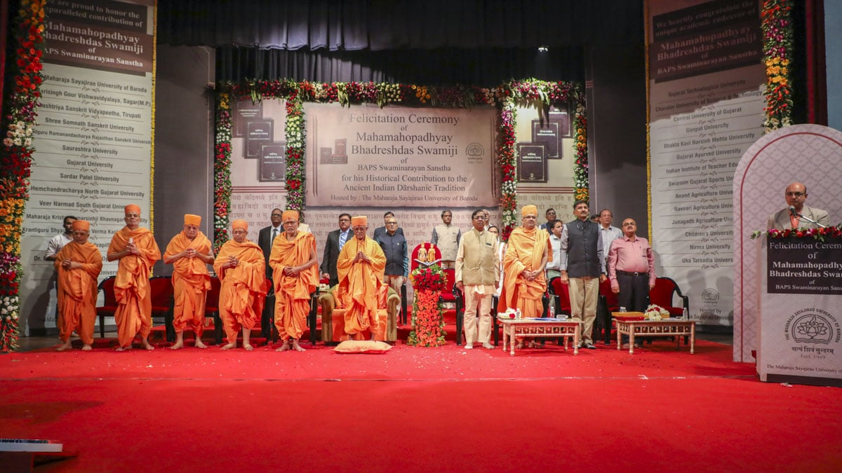Senior sadhus, vice chancellors and university representatives stand for the national anthem