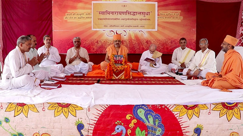 Sadhu Bhadreshdas Swami and Sadhu Munivatsaldas Swami accompanied by an assembly of esteemed scholars