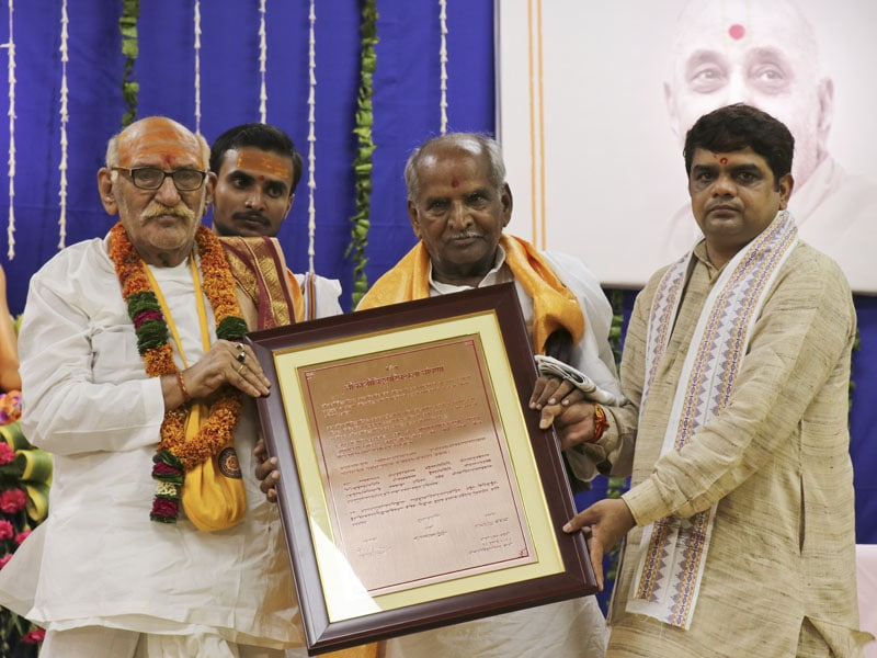 Distinguished Pandits of Shri Kāśī Vidvat Pariṣad present the copper-plated letter of declaration to Mahāmahopādyāya Sadhu Bhadreshdas Swami
